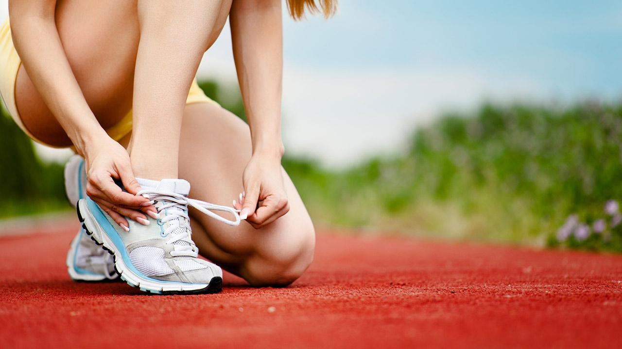 Sportschuhe im Test - Teuer oder Preiswert - Frau bindet sich die Sportschuhe