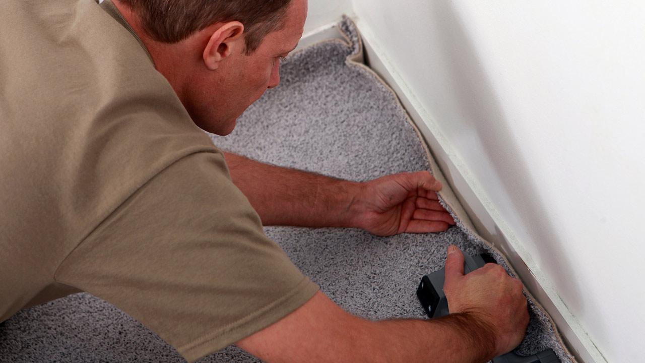 Boden verlegen -So einfah gehts - ein Mann verlegt einen Teppichboden