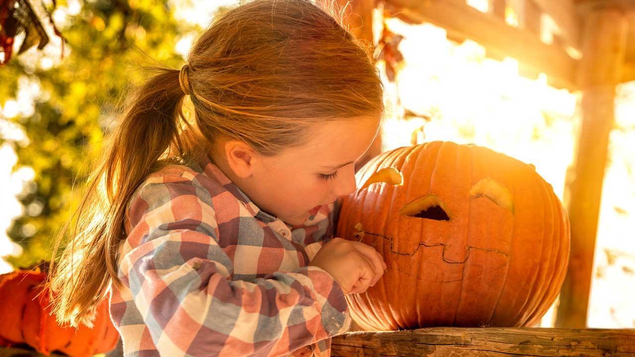 Die schönsten Halloween Deko-Ideen für Garten und Terrasse - Mädchen beim Kürbis Aushöhlen