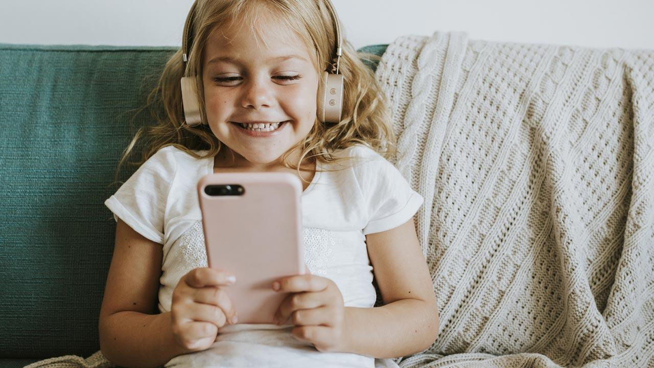 Verzicht aufs Handy zur Fastenzeit - kleines Mädchen mit Mobiltelefon