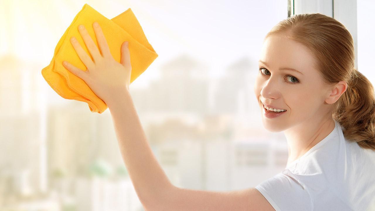 Frühlingsfensterputz ohne Chemie - Hausfrau mit Lächeln