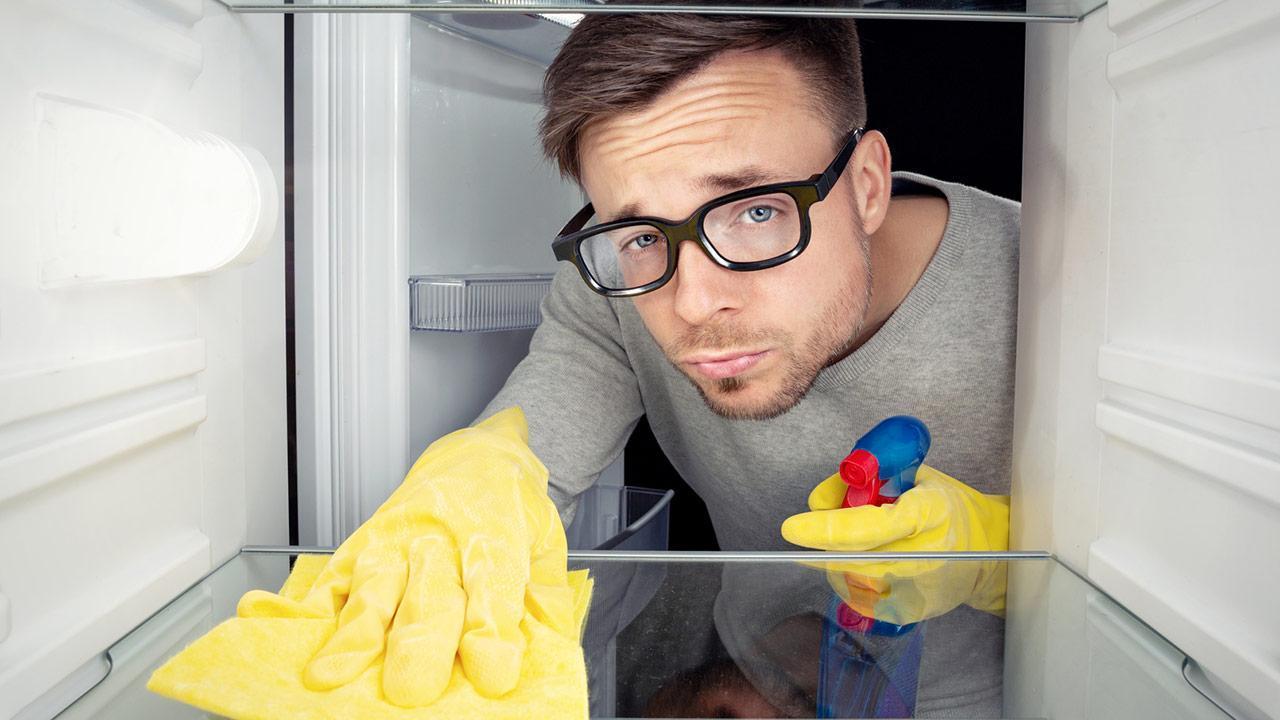 Frühjahrsputz im Kühlschrank  - Mann putzt