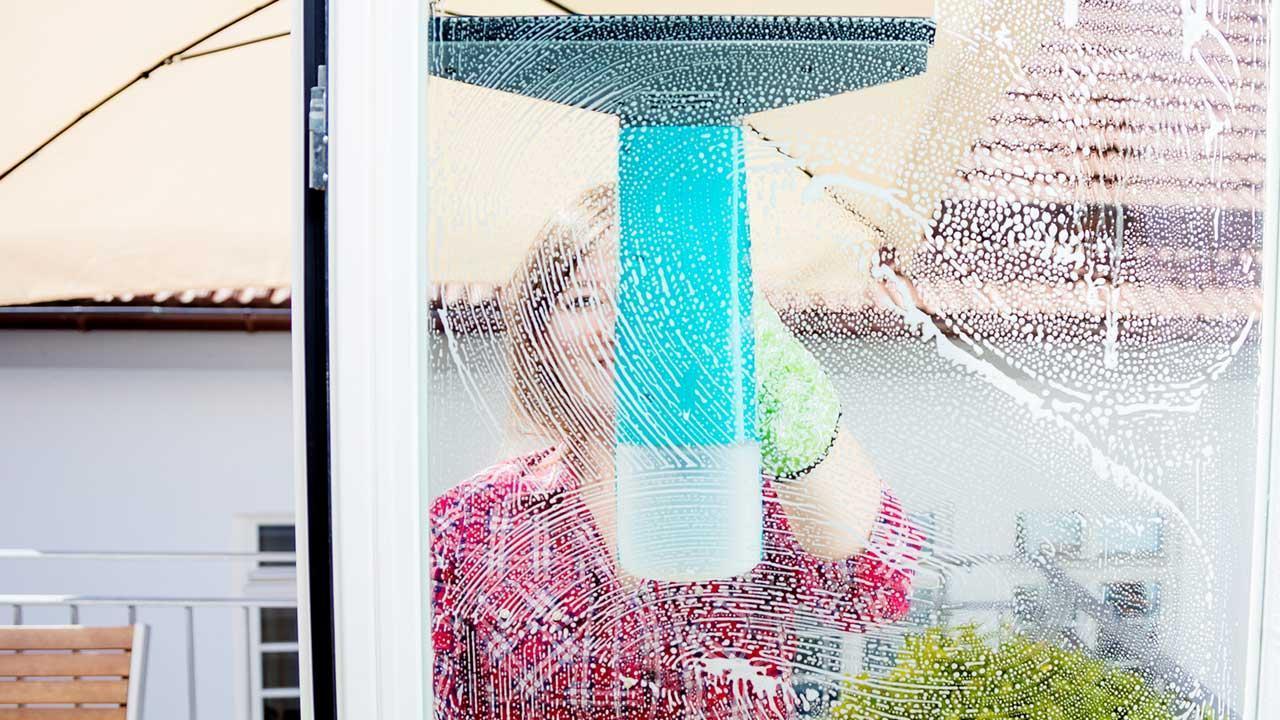 Fenster einfacher putzen mit Fenstersauger - Frau putzt von außen