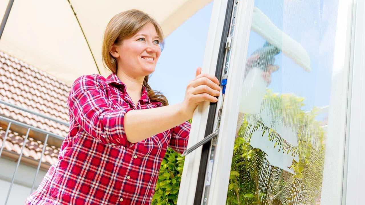 Fenster einfacher putzen mit Fenstersauger - Frau putzt im Sonnenschein