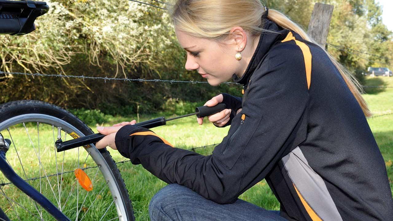 Fahrradreifen ohne Schlauch - Frau pumpt Reifen auf