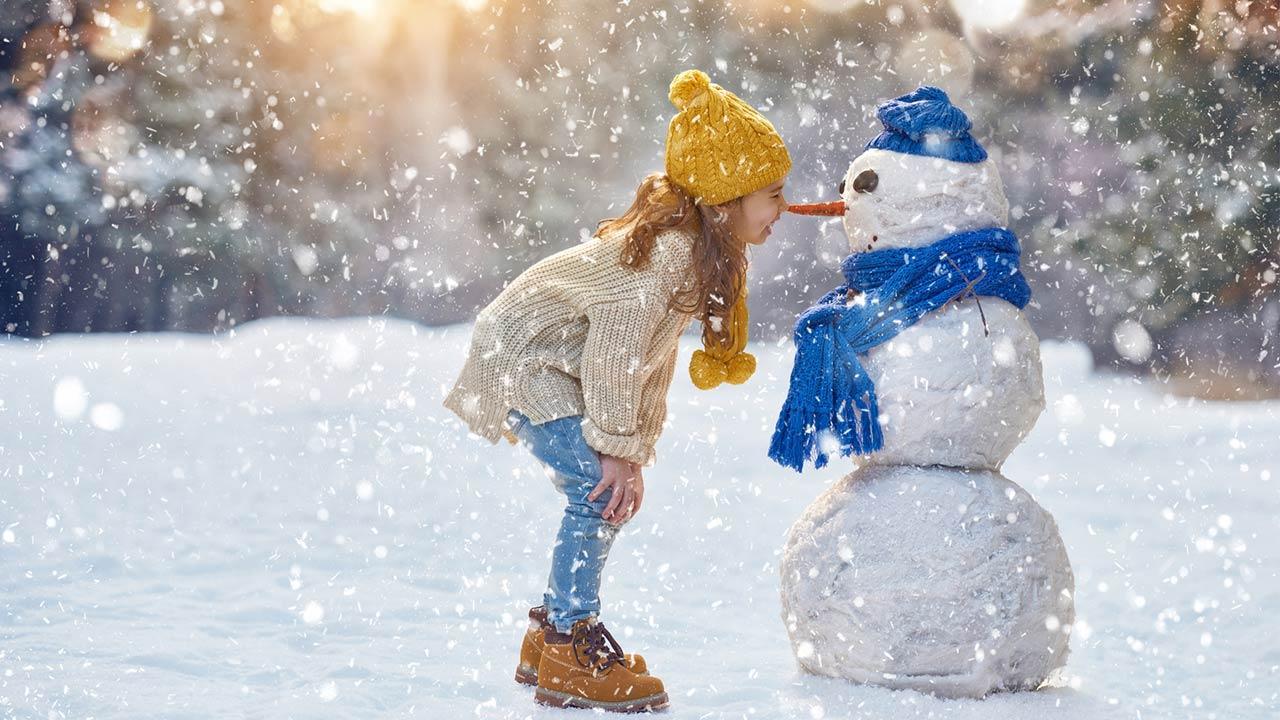 Mit den Kindern einen Schneemann bauen - Mädchen
