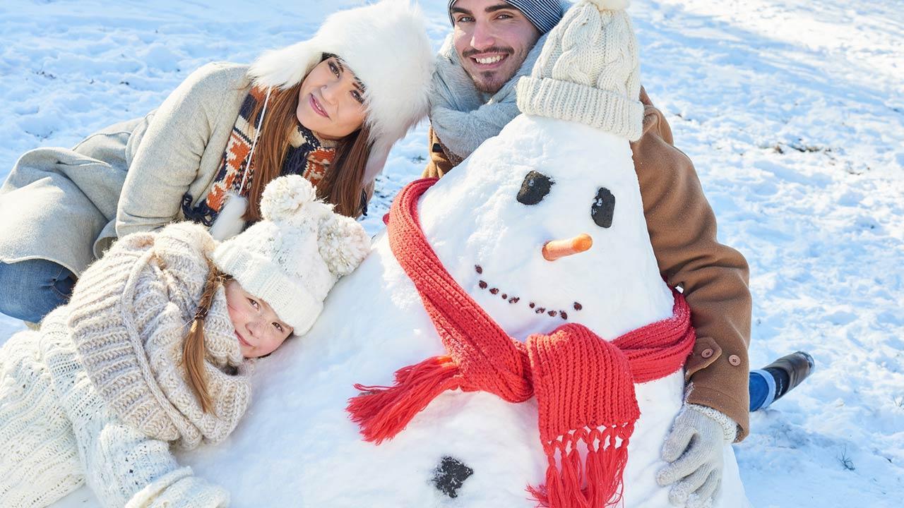 Mit den Kindern einen Schneemann bauen - Familie im Schnee