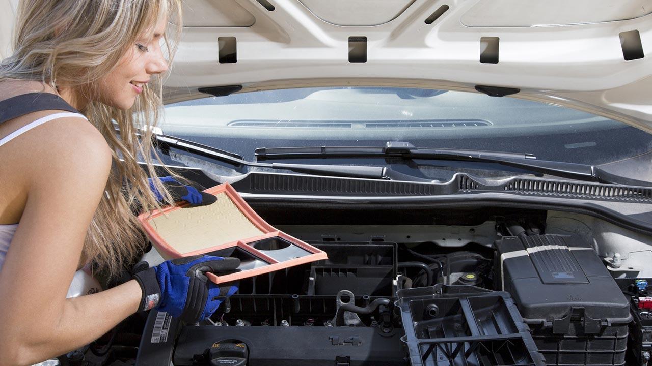 Luftfilter im Auto austauschen - Frau mit Handschuhen