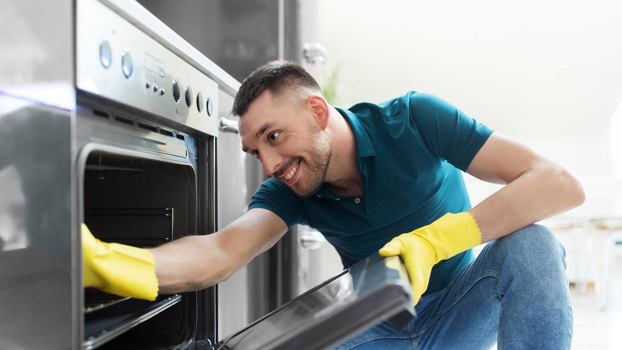 Den Backofen richtig reinigen - junger Mann mit gelben Handschuhen
