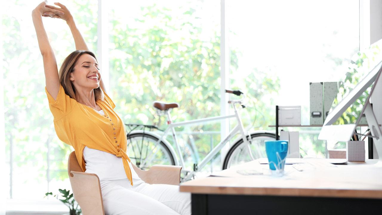 Tipps gegen Rückenschmerzen - der richtige Arbeitsplatz - Frau streckt sich