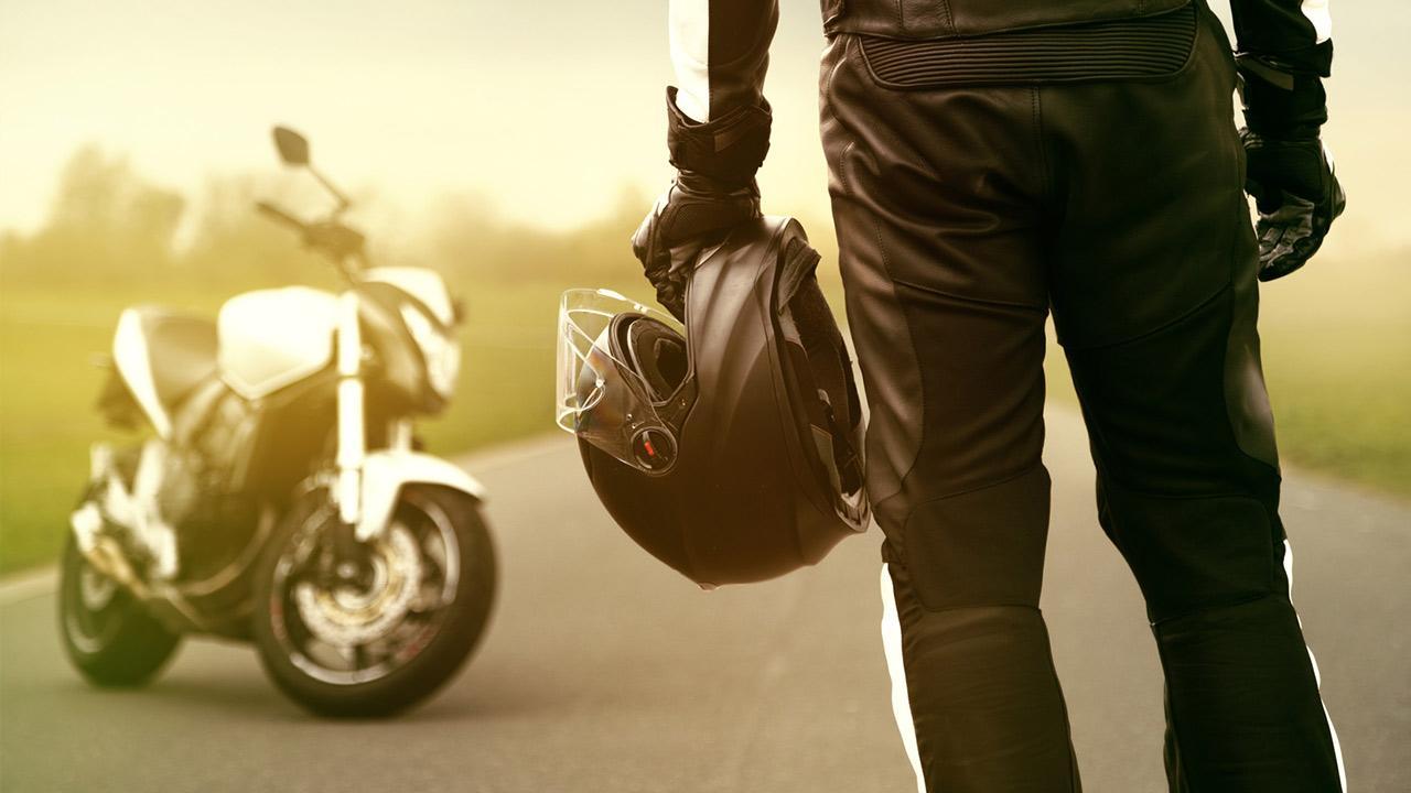 Motorradhelm - worauf muss ich achten? / Mann mit Helm neben einem Motorrad