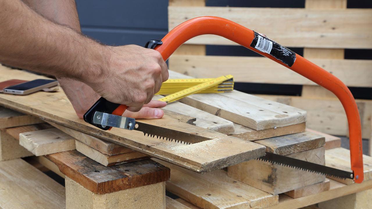 Gartenmöbel aus Paletten selbstgemacht / Mann sägt Holz