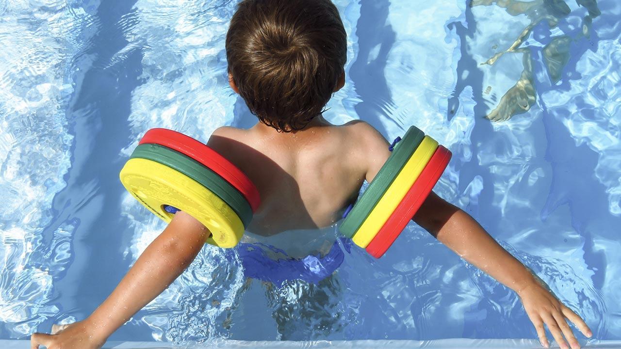 Die besten Schwimmhilfen für Kinder / kleiner Junge mit Schwimmscheiben