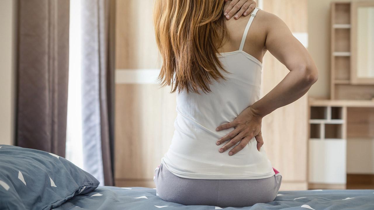 Tipps gegen Rückenschmerzen - Soforthilfe bei akuten Rückenschmerzen / Frau sitzt am Bett und hält ihren Rücken