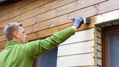 Fenster neu streichen - was ist zu beachten / Mann streicht den Rand des Fensters
