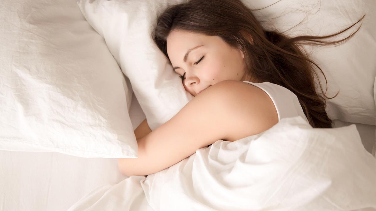 Tipps für guten Schlaf trotz Sommerhitze / Frau schläft im Bett