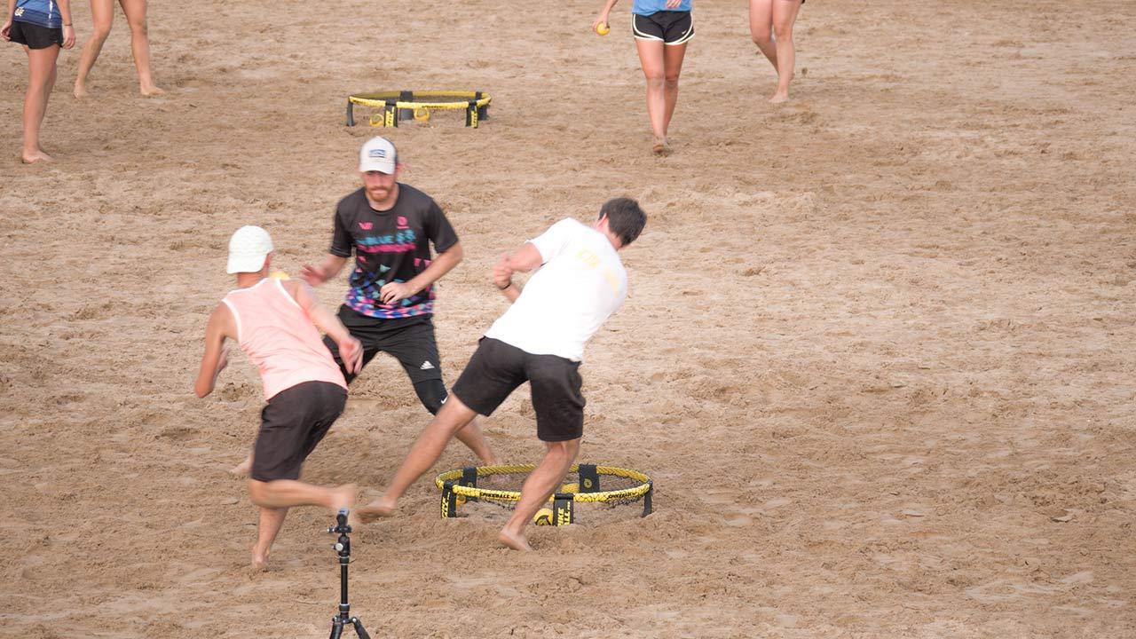 Spikeball - Volleyball mit Trampolin / Leute spielen Spikeball am Strand