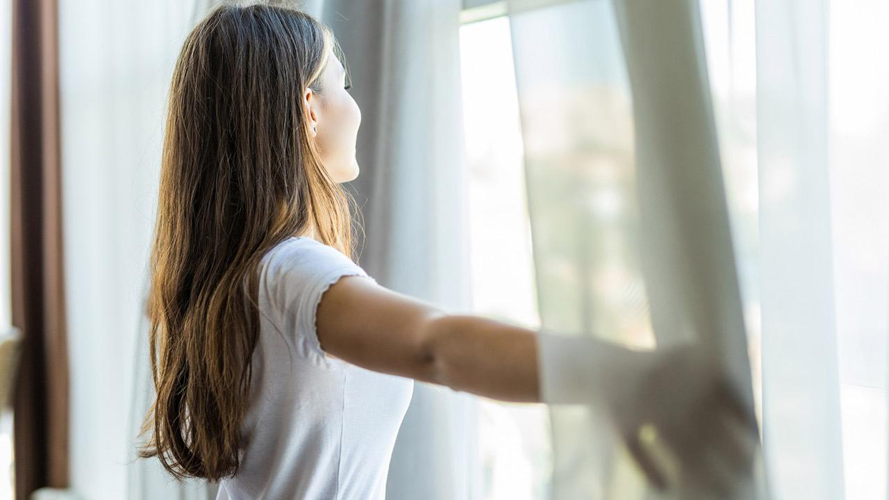 Abkühlung im Haus schaffen ohne Strom / Frau lüftet