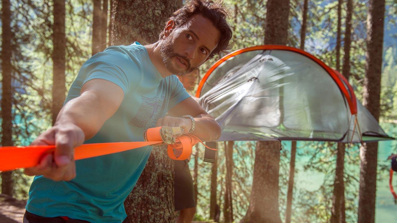Baumzelte - eine außergewöhnliche Übernachtungsmöglichkeit / ein Mann befestigt ein Baumzelt