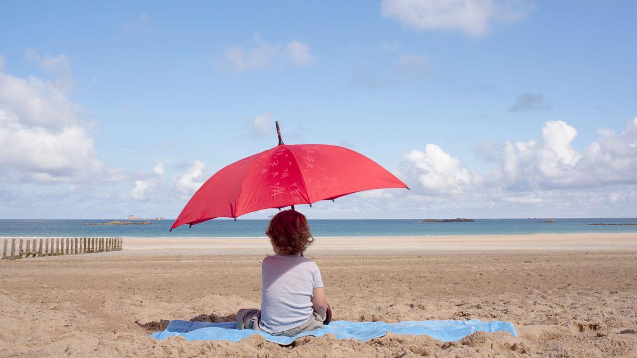 Der passende Sonnenschutz für mein Kind / ein kleines Kind sitzt unter einem Sonnenschirm