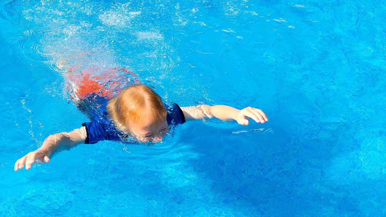 Der passende Sonnenschutz für mein Kind / kleiner Junge schwimmt mit T-Shirt
