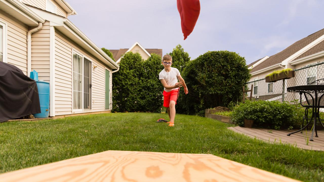 Cornhole - Sandsack werfen im eigenen Garten / eine Person spielt Cornhol