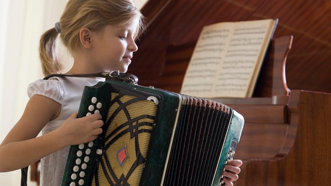Akkordeon spielen - So legen Sie los / ein kleines Mädchen spielt Akkordeon
