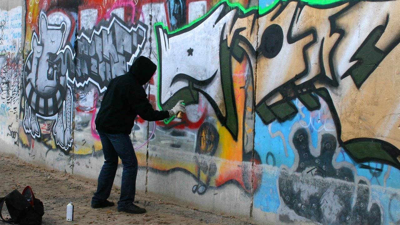 Graffiti - Einstieg in die Hobby-Malerei / ein Mann sprüht Graffiti