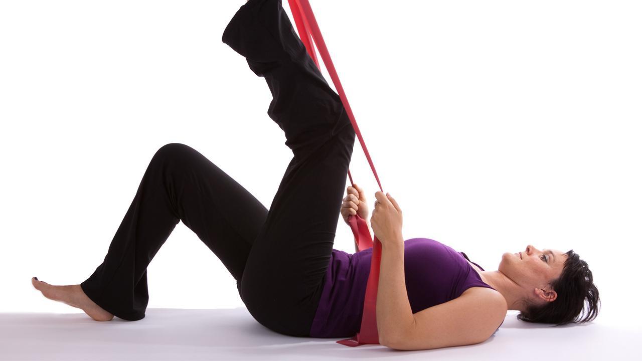 Training mit dem Theraband - Sport für Zuhause / eine Frau trainiert mit Therabänder ihr Bein