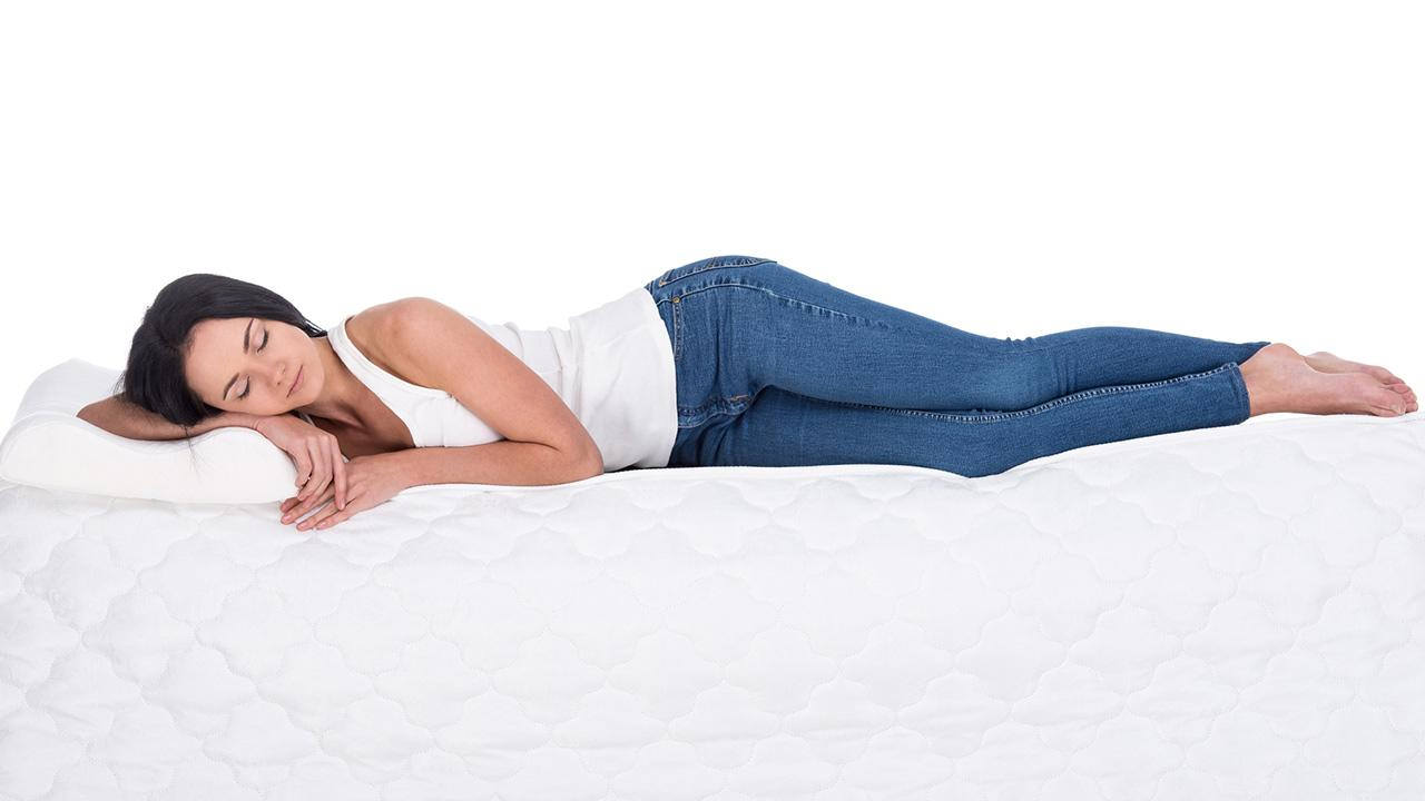 Tipps gegen Rückenschmerzen - eine gute Matratze / Frau liegt auf einer Matratze