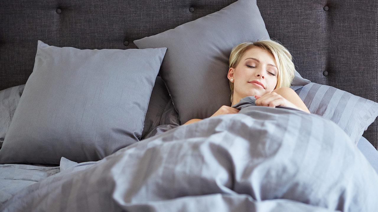 Warme Bettwäsche im Winter-Welche Materialien sind die Besten / Frau liegt im Bett