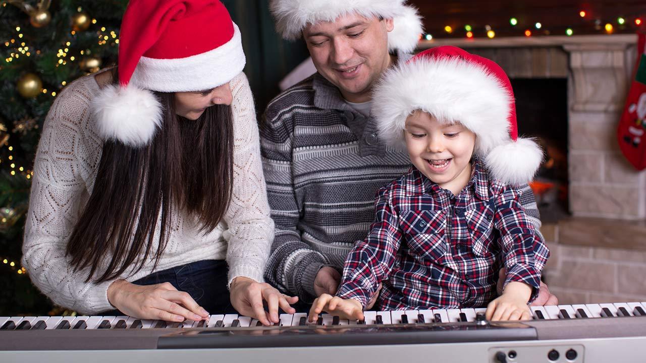 Die schönsten Weihnachtslieder / Eltern spielen mit ihrem Kind am Klavier Weihnachtslieder