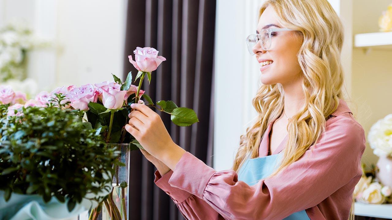Wie ihre Valentinstagsrosen länger frisch bleiben / eine Frau gibt Rosen in die Vase