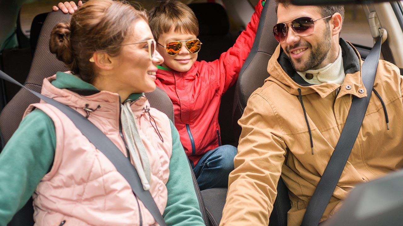 Wochenendausflug - Auto oder Bahn / Familie sitzt im Auto