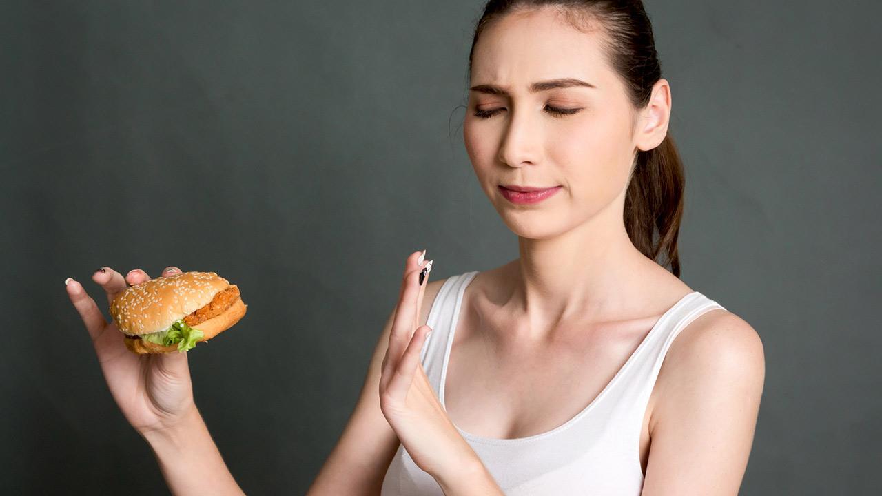 So bereiten Sie sich perfekt aufs Fasten vor - Frau hält einen Burger in der Hand