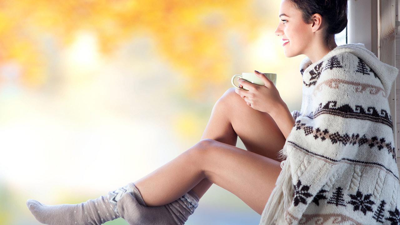 Das Cape die Perfekte Übergangsbekleidung - eine Frau sitzt mit Cape am Fenster