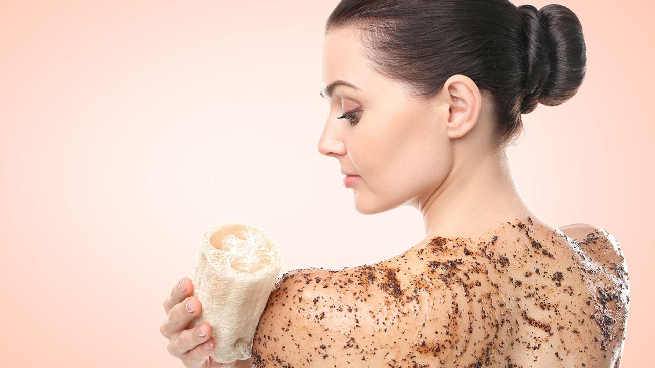 DIY Peeling  - Frau trägt selbstgemachtes Kaffeepeeling auf